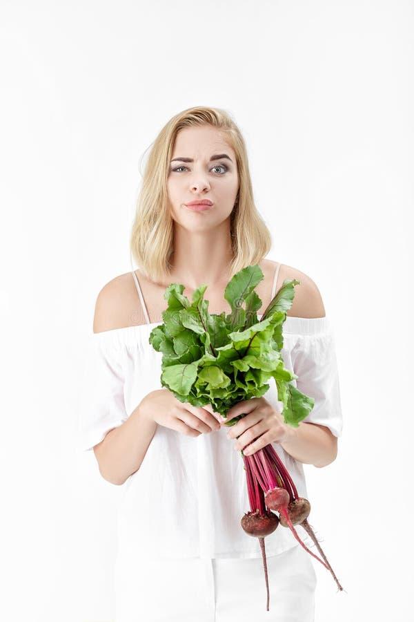 La mujer rubia contrariedad sostiene las remolachas con las hojas verdes en el fondo blanco Salud y vitaminas imagen de archivo libre de regalías