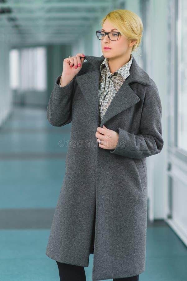 La mujer rubia de la moda vistió el soporte de la capa en pasillo imagen de archivo