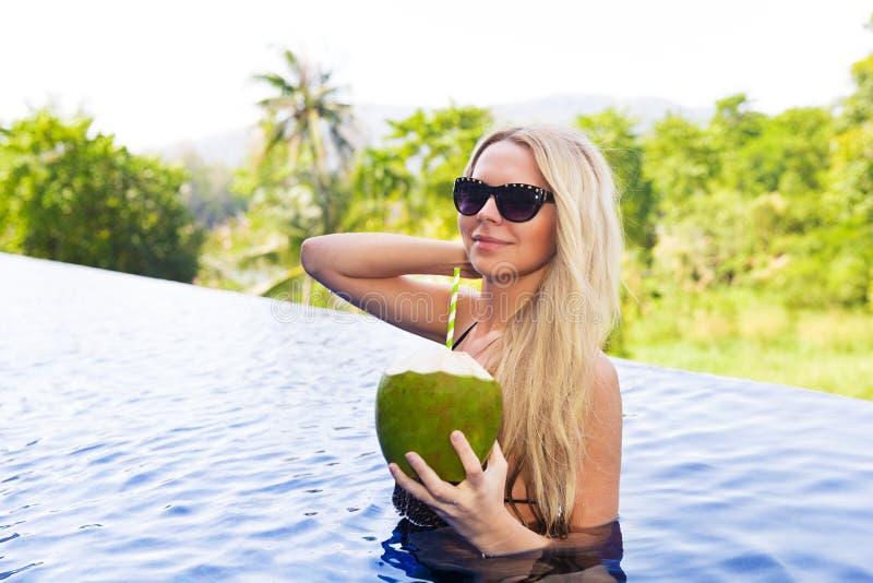 La mujer rubia delgada joven en gafas de sol bebe el cocon sano del detox imágenes de archivo libres de regalías