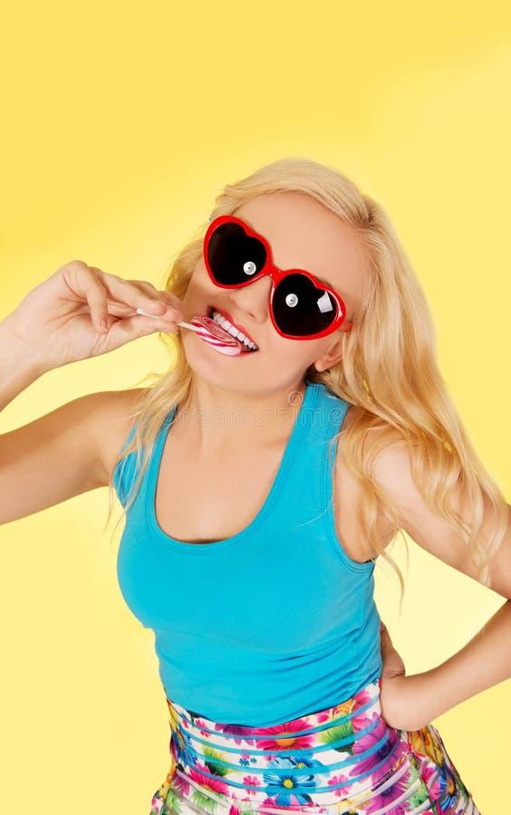 La mujer rubia divertida muerde el lillipop foto de archivo libre de regalías