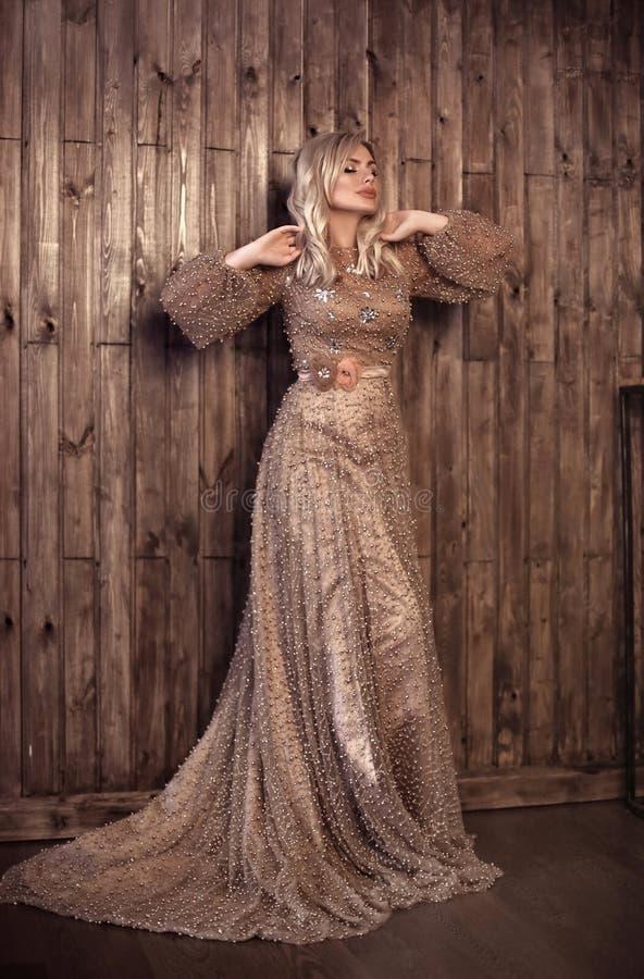 La mujer rubia elegante en perlas beige viste la presentación contra fondo de madera de la pared con área de espacio de la copia  fotografía de archivo libre de regalías