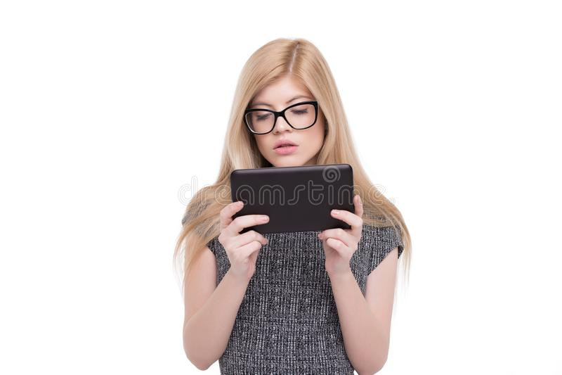 La mujer rubia elegante joven en desgaste formal usando el retrato de la tableta es foto de archivo