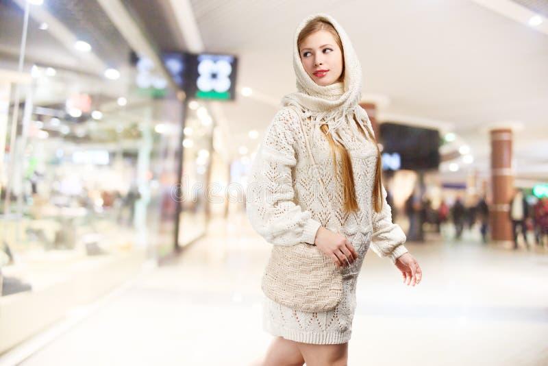 La mujer rubia elegante sonriente de los jóvenes en blanco hizo punto la bufanda con f imagen de archivo libre de regalías