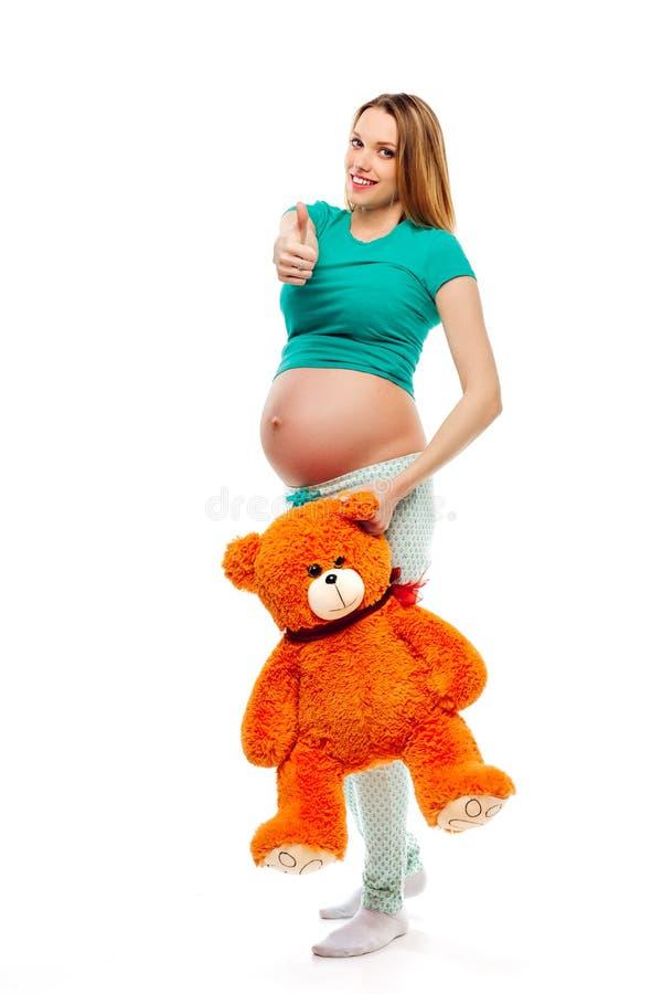 La mujer rubia embarazada hermosa en los pijamas que sostienen un oso del juguete y que muestran manosea con los dedos encima de  imagenes de archivo