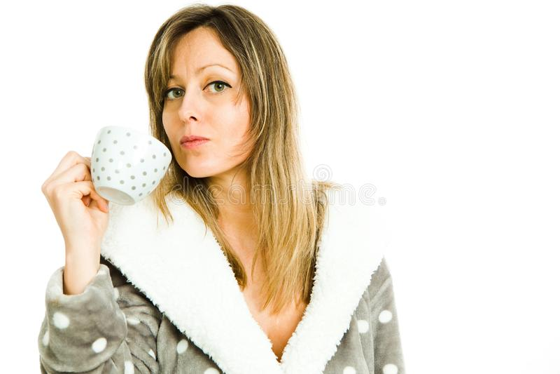 La mujer rubia en bata gris con los puntos blancos bebe blanco fotos de archivo libres de regalías