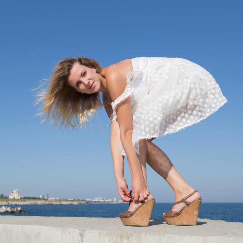 La mujer rubia en el vestido blanco abotona sus sandalias fotos de archivo