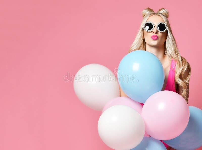 La mujer rubia en la fiesta de cumpleaños que se divierte con los balones de aire del color en colores pastel sopla beso en gafas foto de archivo