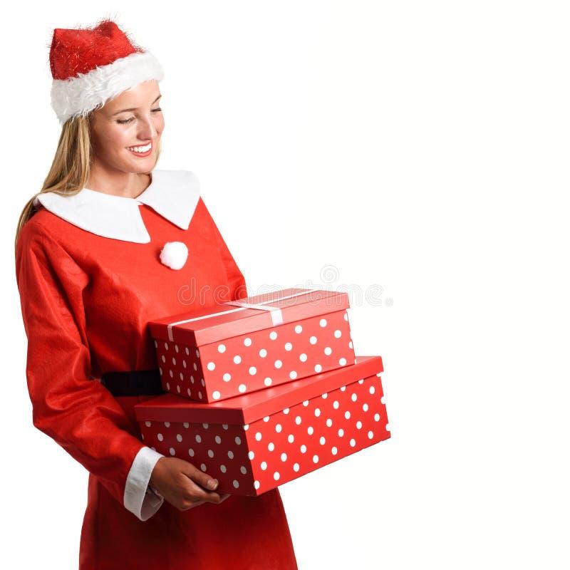 La mujer rubia en Santa Claus viste la sonrisa con las cajas de regalo fotos de archivo libres de regalías