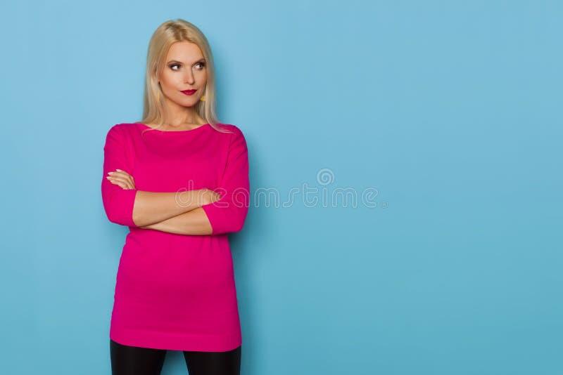 La mujer rubia en suéter rosado está sosteniendo los brazos cruzados y está mirando lejos imágenes de archivo libres de regalías