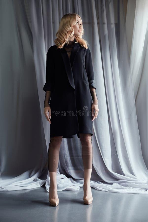 La mujer rubia en una capa negra del otoño se coloca cerca de una ventana grande Ropa de la moda del otoño, pelo rizado hermoso y fotografía de archivo