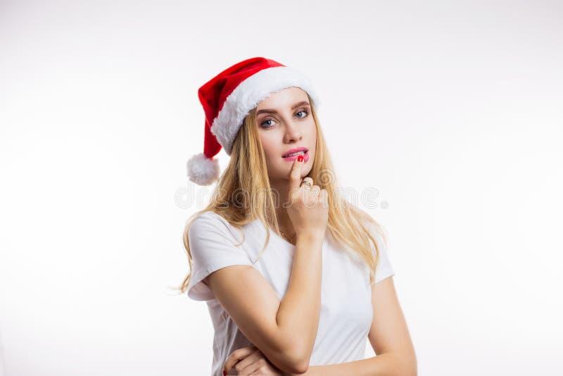 La mujer rubia encantadora en el sombrero de Papá Noel mira la cámara y piensa en el fondo blanco fotos de archivo libres de regalías