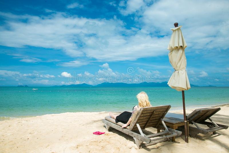 La mujer rubia está mintiendo en un deckchair en la playa imagen de archivo