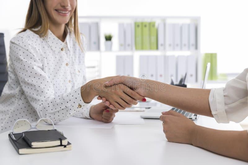 La mujer rubia está sacudiendo las manos con su socio de la pantalla fotografía de archivo libre de regalías