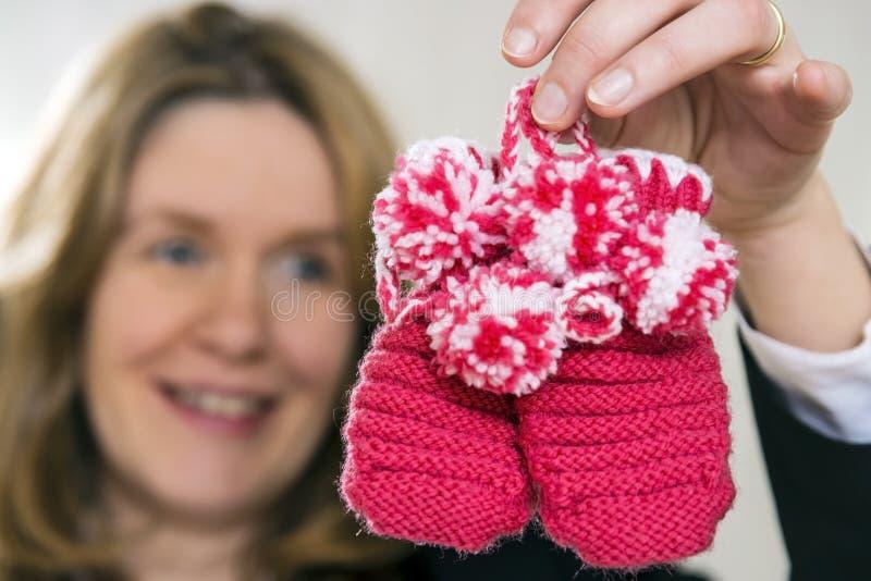 Mujer rubia con los zapatos de bebé imágenes de archivo libres de regalías