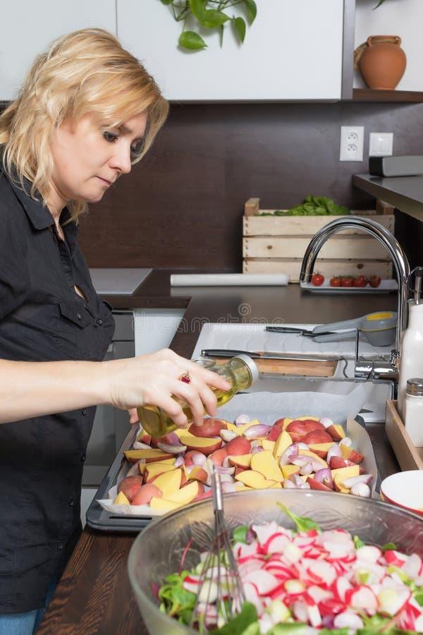 La mujer rubia fresca está preparando las patatas asadas fotos de archivo