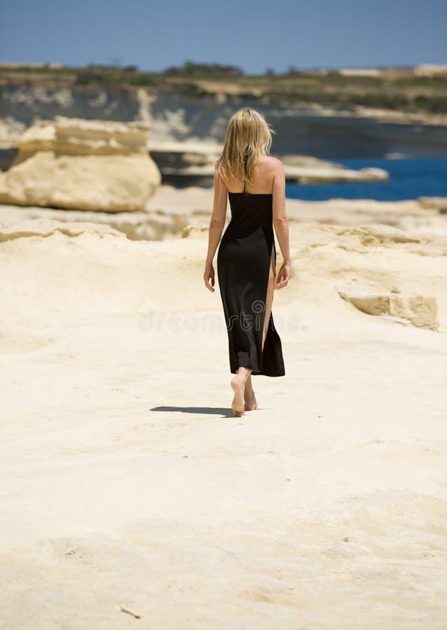 La mujer rubia hermosa camina el pie desnudo ausente, en vestido largo atractivo en la playa de Malta imágenes de archivo libres de regalías