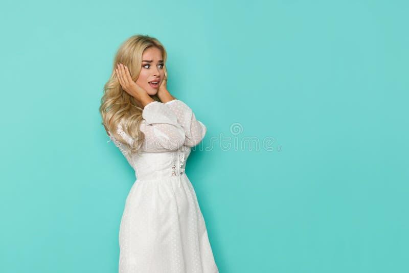 La mujer rubia hermosa chocada en el vestido blanco está llevando a cabo la cabeza en manos y está mirando lejos fotos de archivo