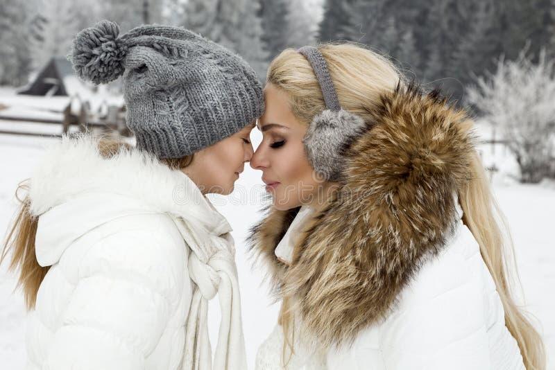 La mujer rubia hermosa con el bebé, la mamá y la hija, en nieve en ropa del invierno y en el fondo es una hermosa vista o imagen de archivo libre de regalías