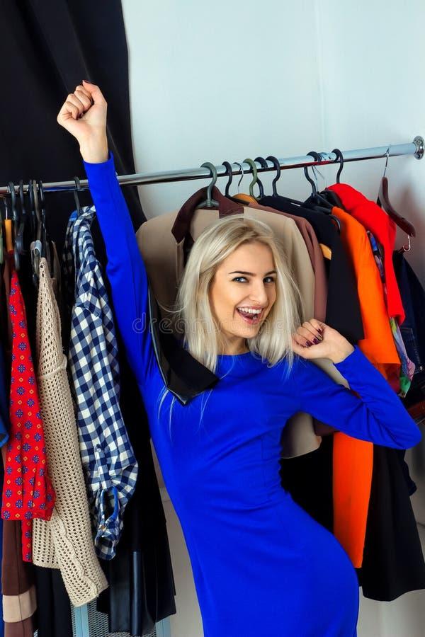 La mujer rubia hermosa de la diversión elige la ropa en tienda imagen de archivo