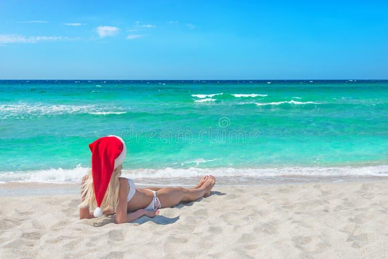 La mujer rubia hermosa en bikini y sombrero rojo de la Navidad en el mar sea imagenes de archivo