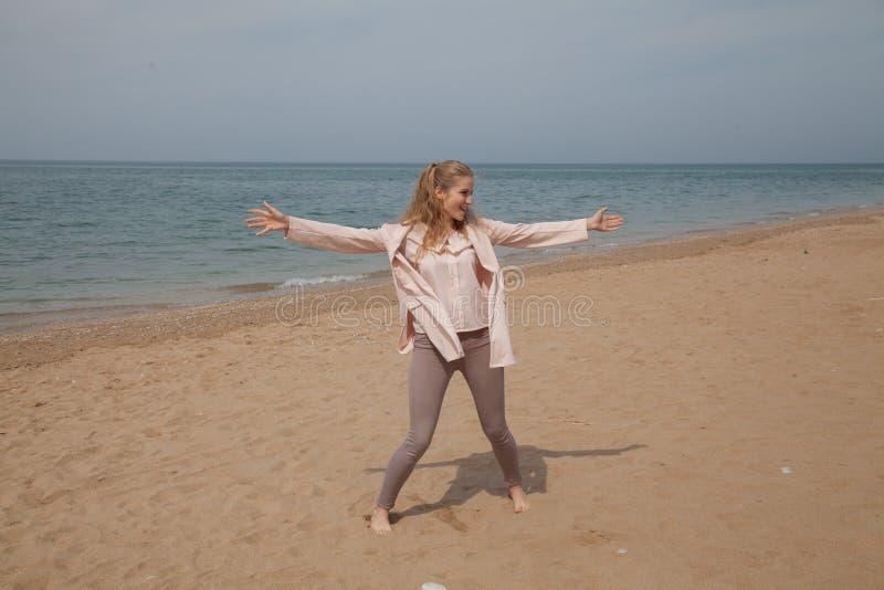 La mujer rubia hermosa en la playa es fresca imagen de archivo