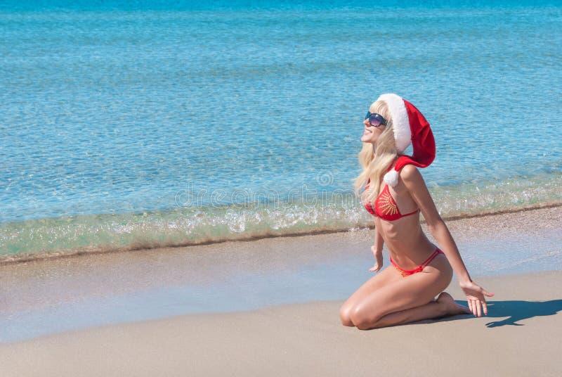 La mujer rubia hermosa en sombrero rojo de la Navidad y el bikini en el mar varan fotografía de archivo