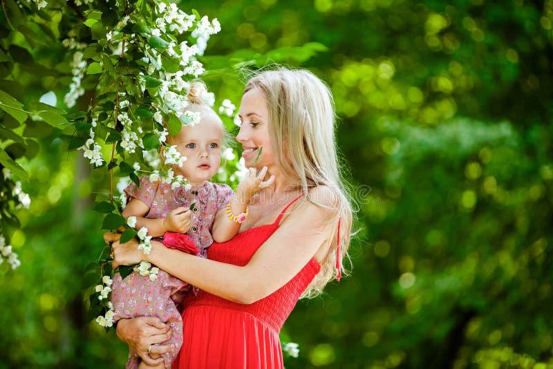 La mujer rubia hermosa en un vestido rojo y la hija están sobre Jas fotos de archivo libres de regalías
