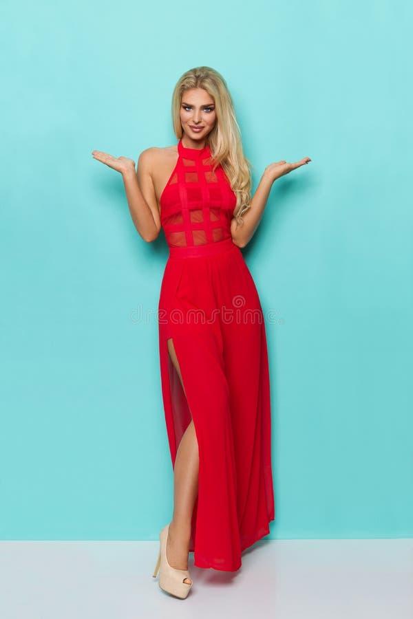 La mujer rubia hermosa en vestido y tacones altos rojos se está colocando con las manos aumentadas imágenes de archivo libres de regalías