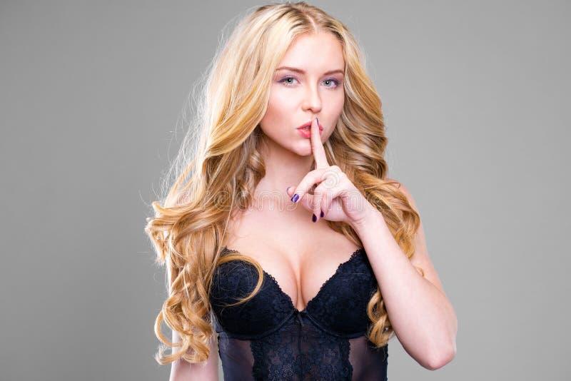 La mujer rubia hermosa joven ha puesto el índice a los labios como muestra del silencio imagen de archivo libre de regalías