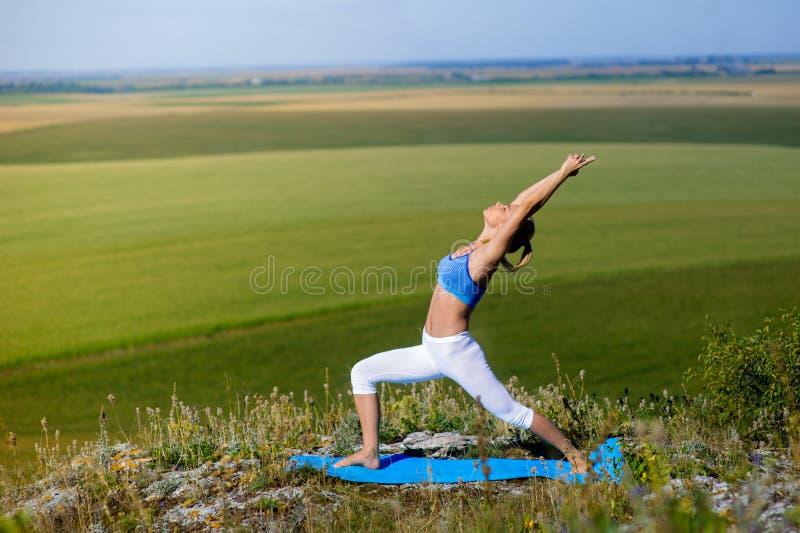 La mujer rubia hermosa joven que hace yoga ejercita en una roca foto de archivo libre de regalías