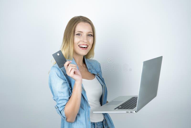 La mujer rubia hermosa parece feliz sosteniendo su tarjeta de banco en un mano y ordenador portátil en otro, en línea haciendo co imagen de archivo