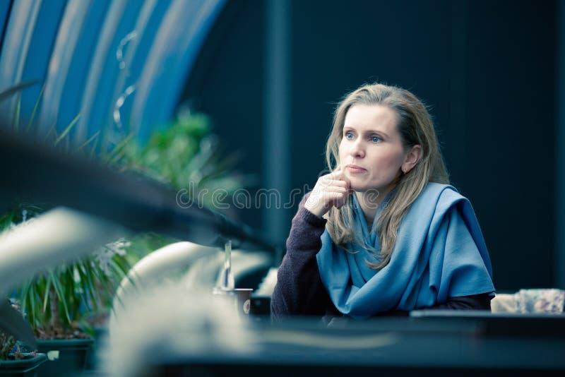 La mujer rubia hermosa se sienta en café imágenes de archivo libres de regalías