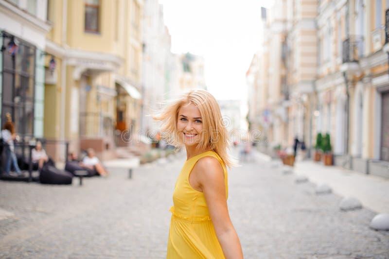 La mujer rubia hermosa se vistió en un vestido amarillo que caminaba alrededor de la ciudad fotografía de archivo libre de regalías
