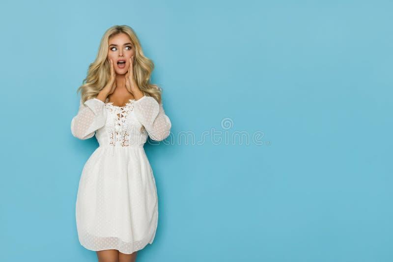 La mujer rubia hermosa sorprendida en el vestido blanco está llevando a cabo la cabeza en manos y está mirando lejos fotos de archivo