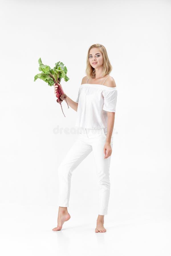 La mujer rubia hermosa sostiene las remolachas con las hojas verdes en el fondo blanco Salud y vitaminas imagen de archivo
