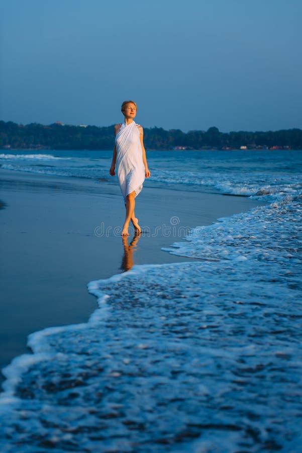 La mujer rubia joven camina descalzo a lo largo de la resaca en el mar en una tarde caliente del verano Luz suave en la puesta de foto de archivo