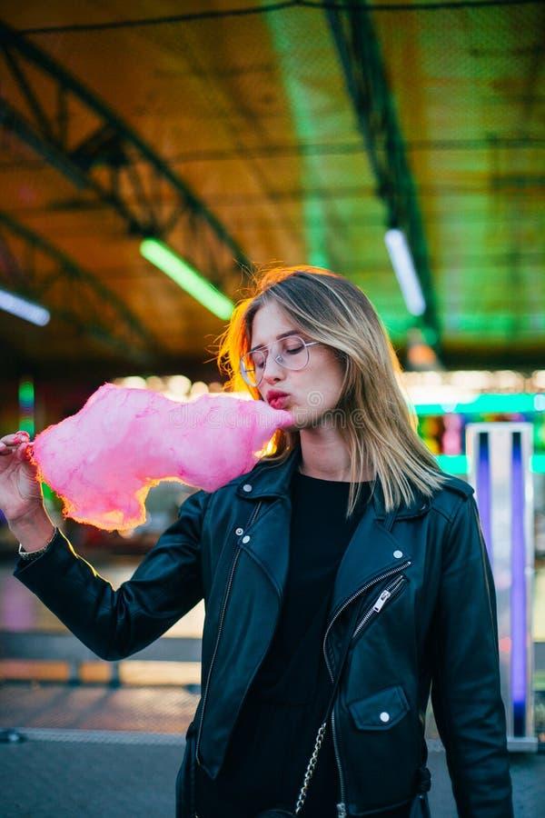La mujer rubia joven come la seda del caramelo de algodón fotografía de archivo libre de regalías