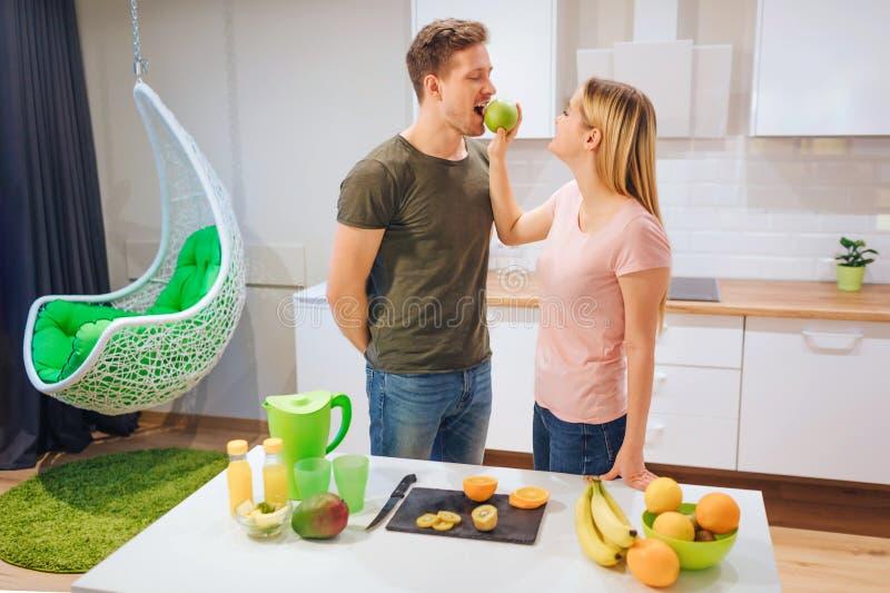La mujer rubia joven da a su marido una manzana orgánica mientras que cocina en la cocina Familia de consumición sana vegetariano imagenes de archivo