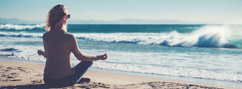 La mujer rubia joven de la vista posterior horizontal de la imagen que se sentaba en la posición de loto dobló el gesto del mudra foto de archivo libre de regalías