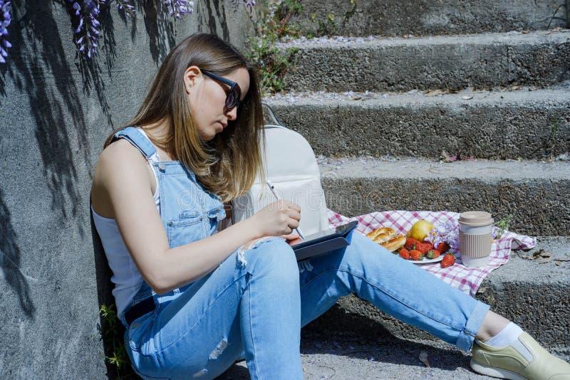 La mujer rubia joven del inconformista en gafas de sol dibuja en una tableta en su fotografía de archivo