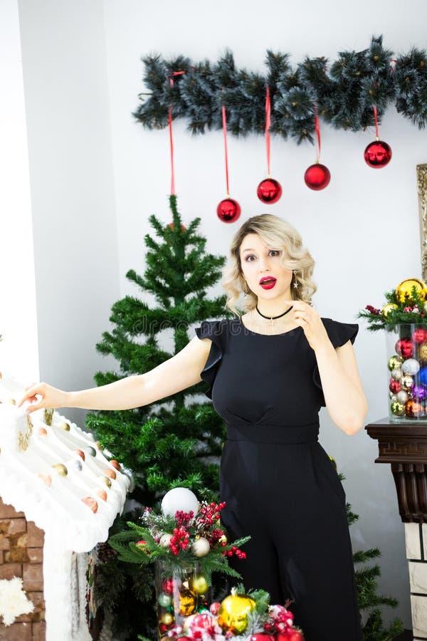 La mujer rubia joven elige decoraciones de la Navidad fotos de archivo libres de regalías