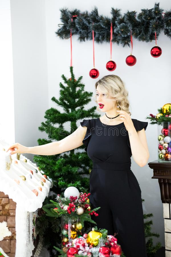La mujer rubia joven elige decoraciones de la Navidad imagen de archivo libre de regalías