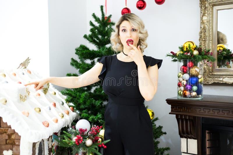 La mujer rubia joven elige decoraciones de la Navidad fotografía de archivo libre de regalías