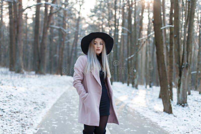 La mujer rubia joven encantadora en una capa elegante de la lila en un vestido negro en un sombrero negro elegante se está coloca fotos de archivo libres de regalías