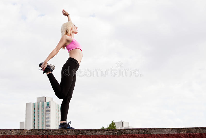 La mujer rubia joven está haciendo posición en cuclillas al aire libre fotografía de archivo libre de regalías