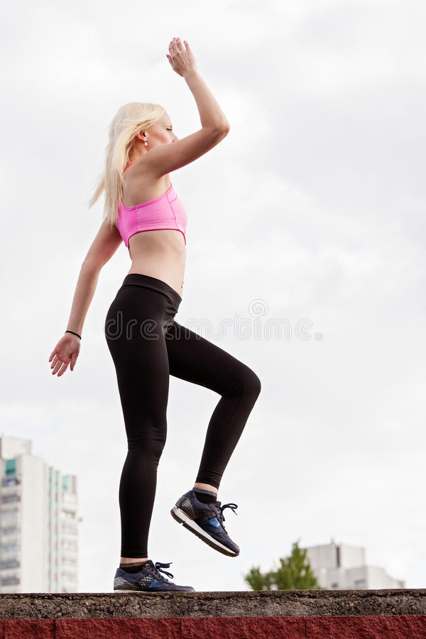 La mujer rubia joven está haciendo posición en cuclillas al aire libre imagenes de archivo
