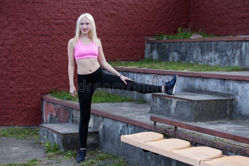 La mujer rubia joven está haciendo posición en cuclillas al aire libre fotos de archivo