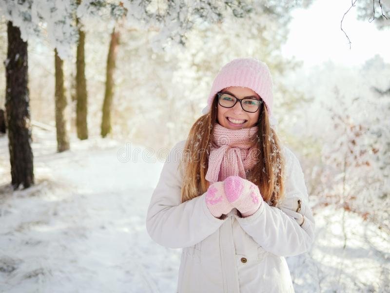 La mujer rubia joven feliz adorable en rosa hizo punto la bufanda del sombrero que se divertía que daba un paseo el bosque nevoso foto de archivo