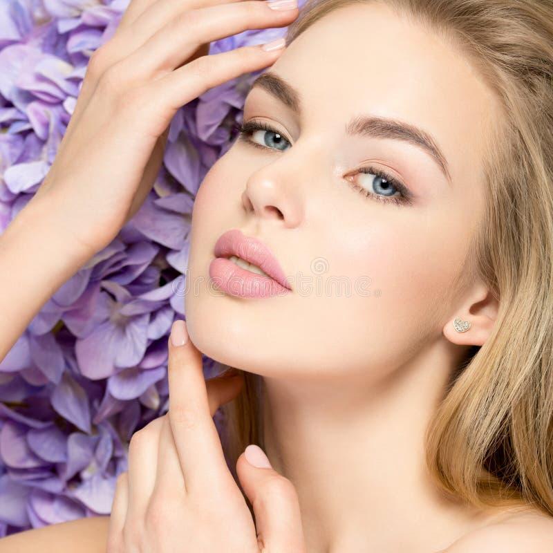 La mujer rubia joven hermosa con las flores acerca a la cara fotos de archivo