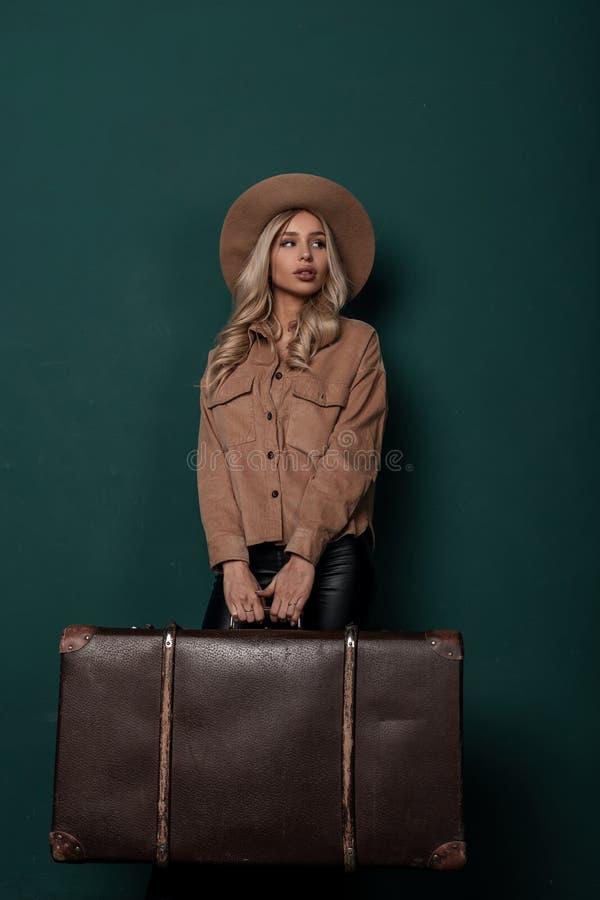La mujer rubia joven hermosa en un sombrero elegante beige en una camisa elegante en los pantalones de cuero se está colocando imagenes de archivo